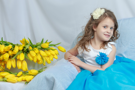The little girl on the sofa with a bouquet of flowers.