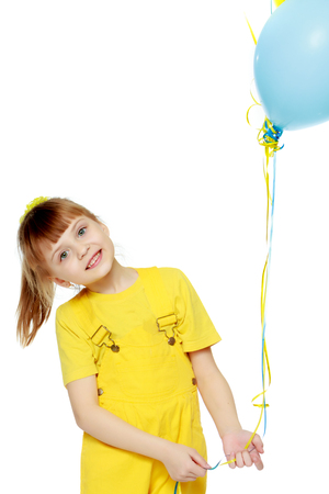 Girl with a short bangs on her head and bright yellow overalls. Фото со стока