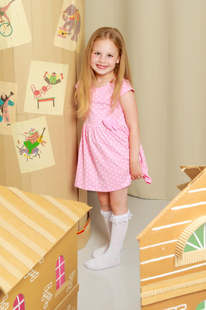 A little girl is playing in a cardboard house