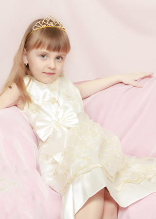 The little princess is sitting on the couch. Stock Photo