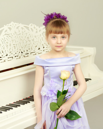 A girl is posing near a white grand piano.