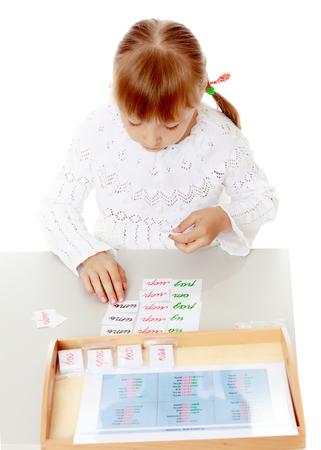 A little girl is studying Montessori stuff.