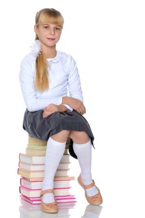 Schoolgirl sitting on a pile of books