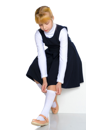A little girl is straightening her stockings.