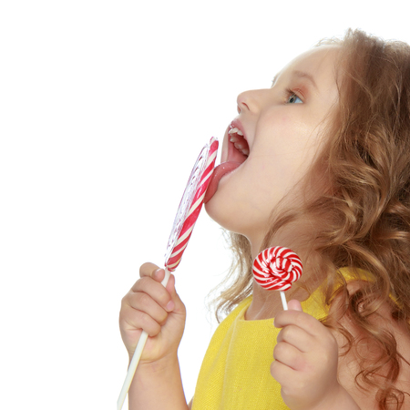 A little girl licks a candy on a stick.