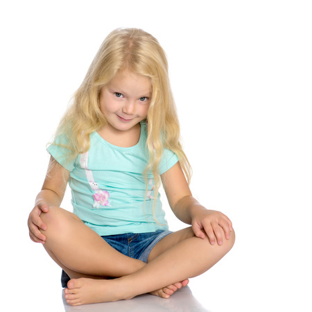 Little girl is sitting on the floor.