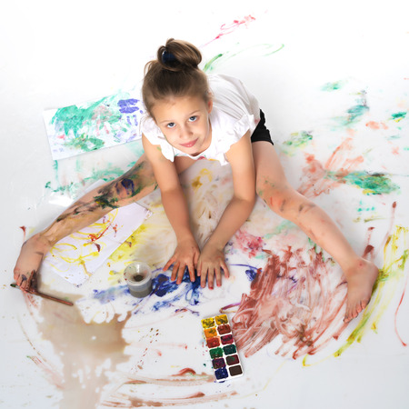 A little girl paints with paint and brush. Imagens