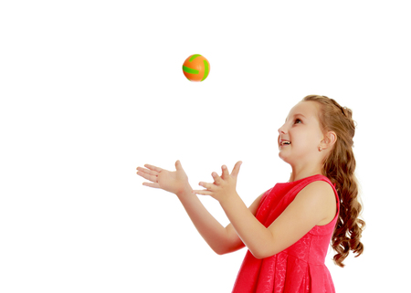 The little girl throws the ball up