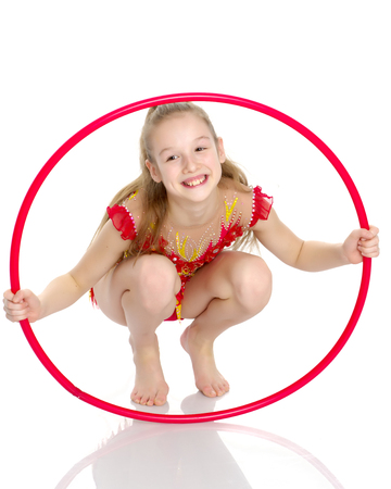 A girl gymnast performs an exercise with a hoop. Standard-Bild - 96583769