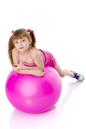 little girl doing exercises on a big ball for fitness. Imagens