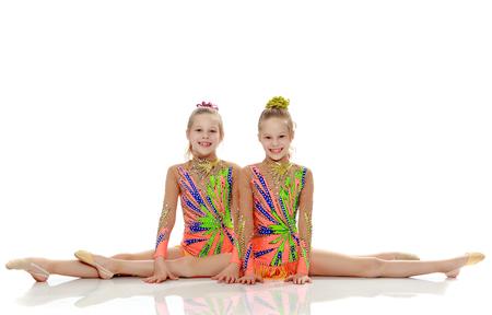 Two girls gymnast sitting on splits. Standard-Bild - 97117789