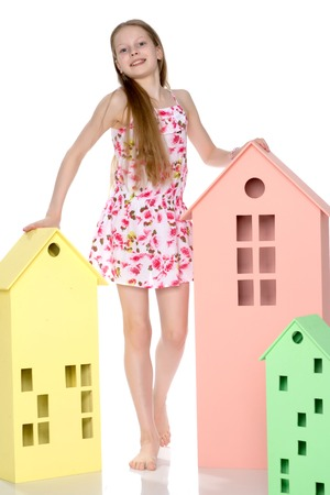 Little girl is playing with wooden houses.