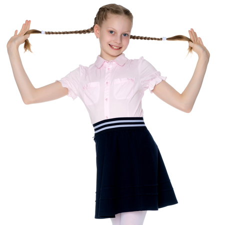 The little girl is pulling herself in pigtails. Foto de archivo