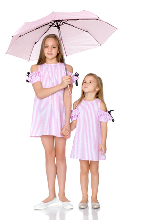 Two girls are standing under umbrellas. Stock Photo