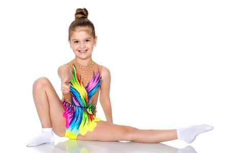 Girl gymnast perform the twine exercise.