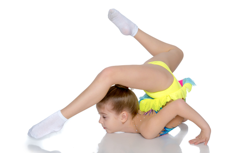 A gymnast performs an exercise stance on her forearms.