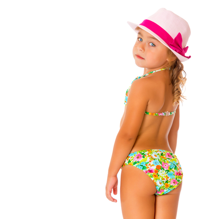 A small tanned girl in a swimsuit and a hat.