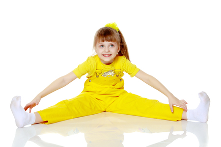 Girl with a short bangs on her head and bright yellow overalls. Stock Photo
