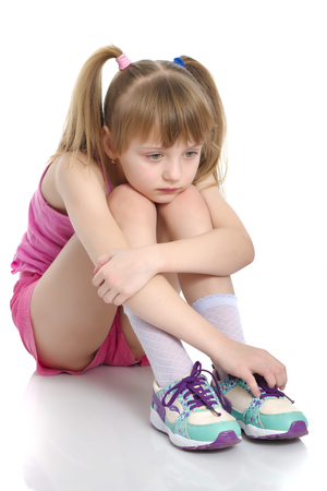 Girl gymnast sits on the floor and cries
