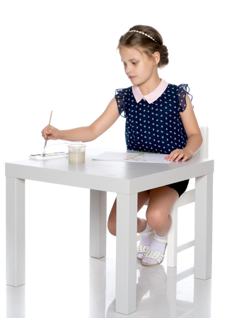 A little girl paints with paint and brush. Stock Photo