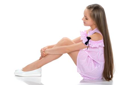 A teenage girl is sitting on the floor. Foto de archivo