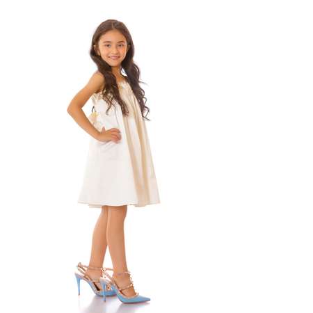 A small Asian girl in high-heeled shoes. Banque d'images