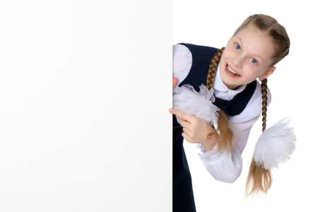 Little girl is showing a finger on a white banner. Stock Photo