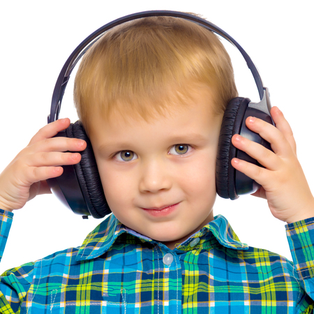 A little boy in big stereo headphones.