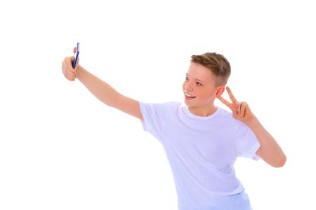 A cheerful little boy is making a selfie.