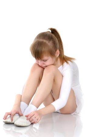 La ginnasta della ragazza si siede sul pavimento e piange