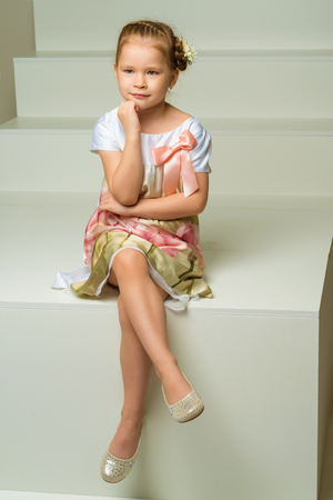 Beautiful little girl is sitting on the white staircase. Banque d'images
