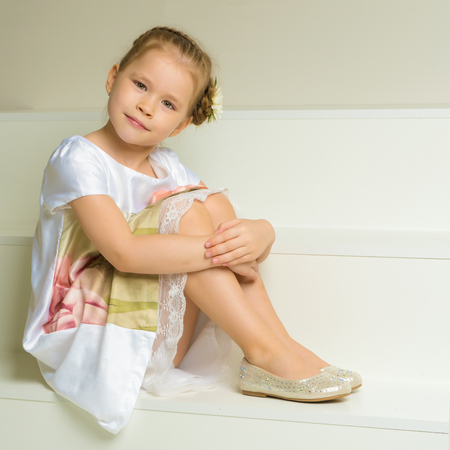 Beautiful little girl is sitting on the white staircase. Stock Photo