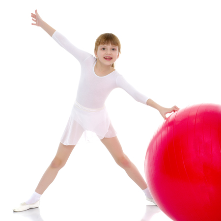 little girl doing exercises on a big ball for fitness. Stock Photo