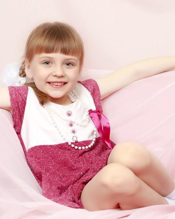Girl sits on a pink sofa. Foto de archivo