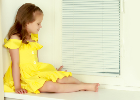 A little girl is sitting by the window with jalousie