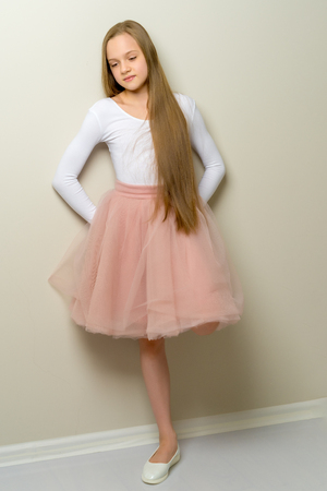 A little girl with long silky hair near the wall. Stock Photo