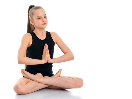 A little girl is meditating in a lotus pose.