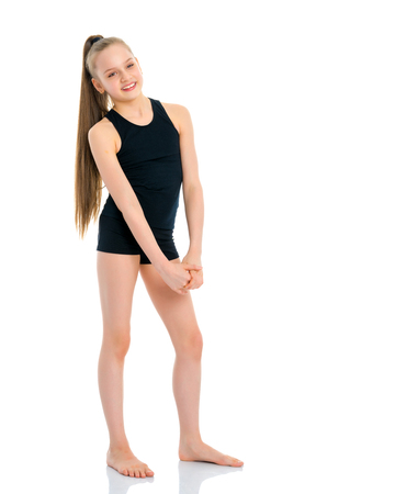 Girl gymnast in a black T-shirt and shorts prepare for the exerc