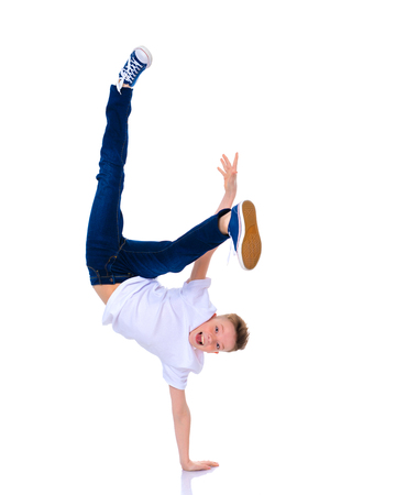A cheerful little boy from school age is dancing breakdance.