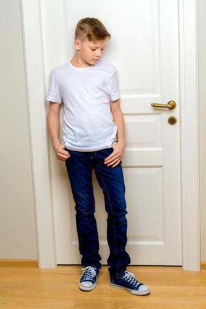 Fashionable little boy near the white door.