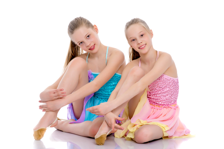 Girls gymnasts sit on the floor. Stock Photo