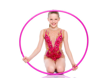 A girl gymnast performs an exercise with a hoop.