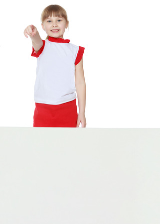 A little girl is looking from behind an empty banner. Stock Photo