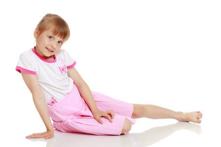 Kleines Mädchen sitzt auf dem Boden.