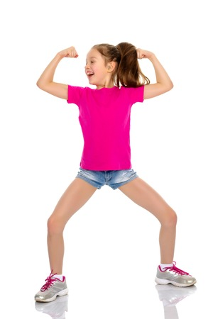 A little girl shows her muscles. Stock Photo