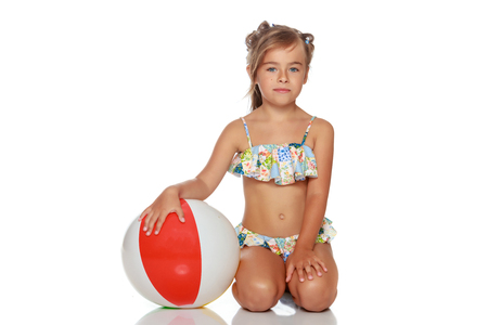 Little girl in a swimsuit with a ball Foto de archivo