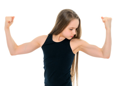 A little girl shows her muscles. Imagens