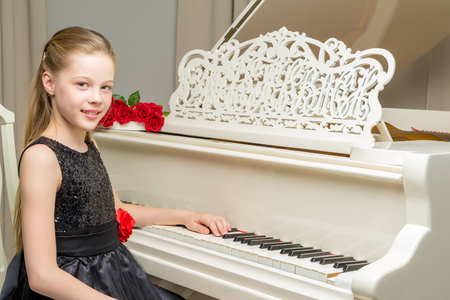 Girl schoolgirl near the piano on which lies a bouquet of flower