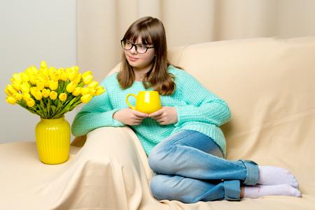 Girl schoolgirl with a mug in her hands.