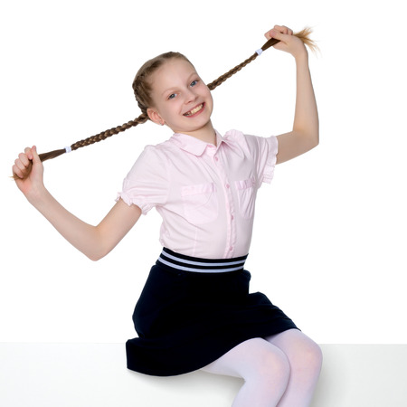 The little girl is pulling herself in pigtails. Stock fotó